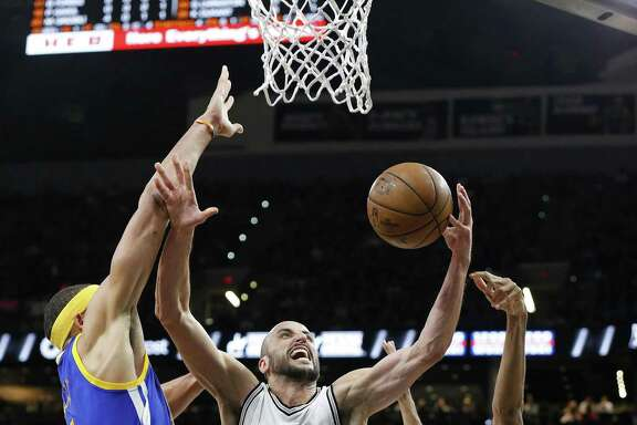 San Antonio Spurs' Manu Ginobili shoots between Golden State Warriors' JaVale McGee (left) and Shaun Livingston during first half action in Game 4 of the Western Conference Finals held Monday May 22, 2017 at the AT&T Center.
