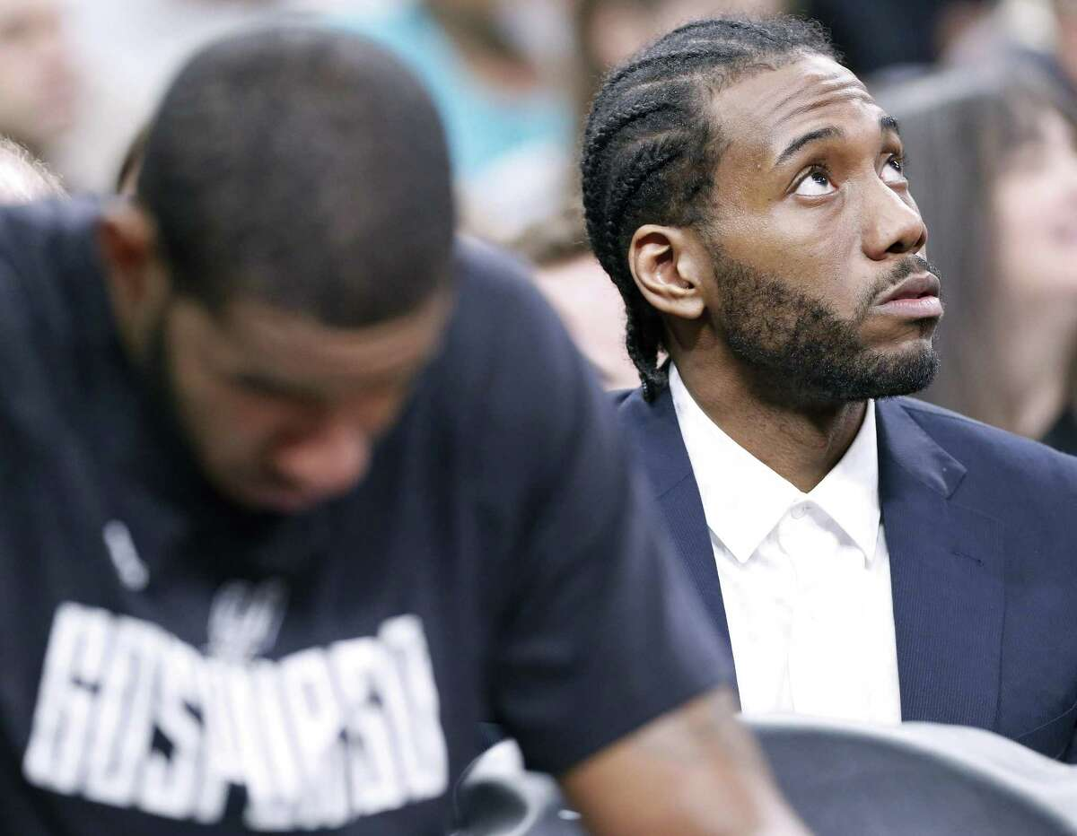 Spurs' LaMarcus Aldridge (left) sits on the bench as teammate Kawhi Leonard sits behind the bench during first half action in Game 4 of the Western Conference finals against the Golden State Warriors on May 22, 2017 at the AT&T Center.