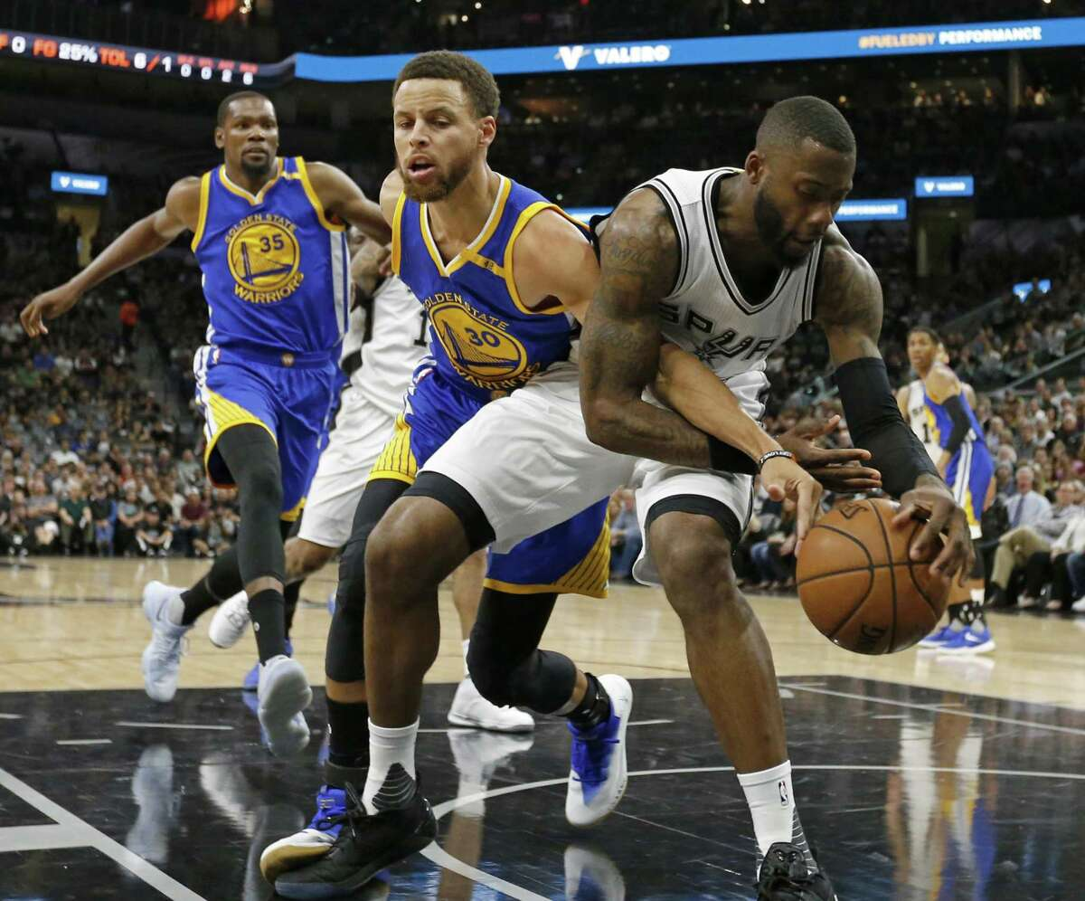 Golden State Warriors' Stephen Curry and the Spurs' Jonathon Simmons battle for a loose ball during first half action in Game 4 of the Western Conference finals on May 22, 2017 at the AT&T Center.