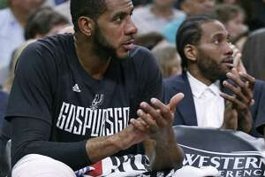 Spurs' LaMarcus Aldridge sits on the bench as teammate Kawhi Leonard sits behind him during Game 4 of the Western Conference finals against the Golden State Warriors on May 22, 2017 at the AT&T Center.