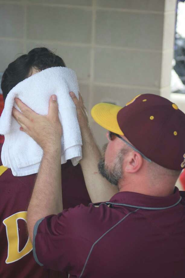 A cold towel provides relief from the muggy conditions for Deer Park first baseman Clay Aguilar during last Saturday's Game 3 showdown with Clear Springs. Applying the iced-down towel to Aguilar's face is trainer David Viaclovsky. Aguilar and Co., now prepare for Ridge Point, starting on Thursday. Photo: Robert Avery