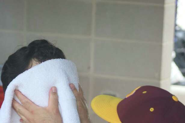 A cold towel provides relief from the muggy conditions for Deer Park first baseman Clay Aguilar during last Saturday's Game 3 showdown with Clear Springs. Applying the iced-down towel to Aguilar's face is trainer David Viaclovsky. Aguilar and Co., now prepare for Ridge Point, starting on Thursday.