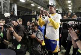 Golden State Warriors' Kevin Durant stands with members of the media using his smartphone to take pictures of his mother, not pictured, posing with the trophy after their 129-115 win over the San Antonio Spurs in Game 4 of the NBA basketball Western Conference finals, Monday, May 22, 2017, in San Antonio. (AP Photo/Eric Gay)