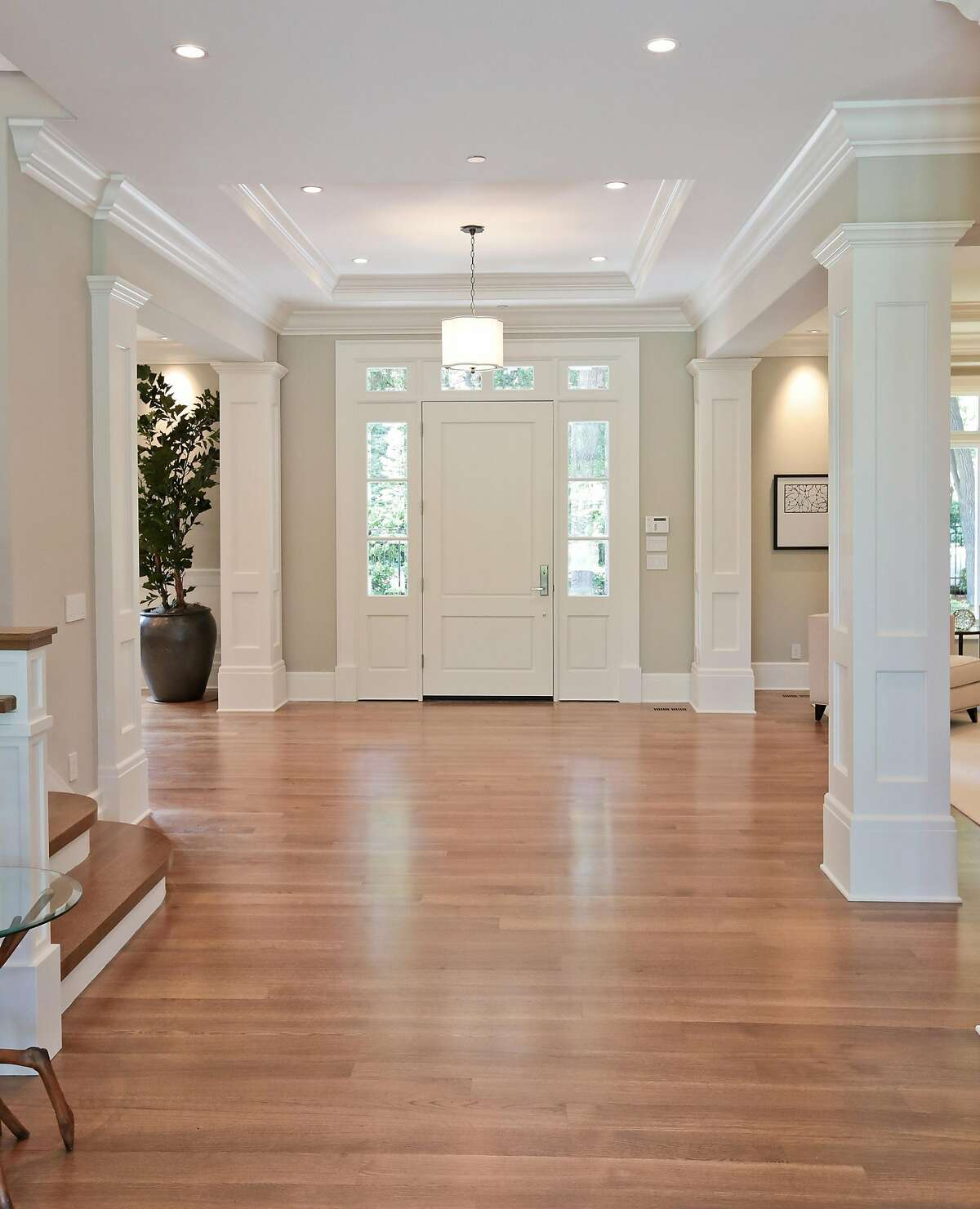 The foyer features rift-sawn white oak flooring and a coffered ceiling with a chandelier.