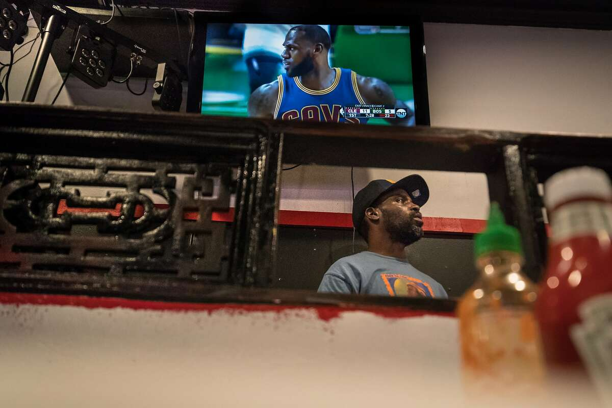 D.J. Jimmie Swagger watches a NBA playoff game on one of the many TV screens as he plays music for the weekly pop up restaurant.