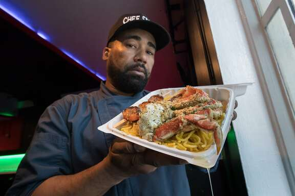 Edward Wooley (Chef Smelly) holds his popular half crab on garlic noodles dish on Friday, May 19, 2017 in Oakland, Calif.