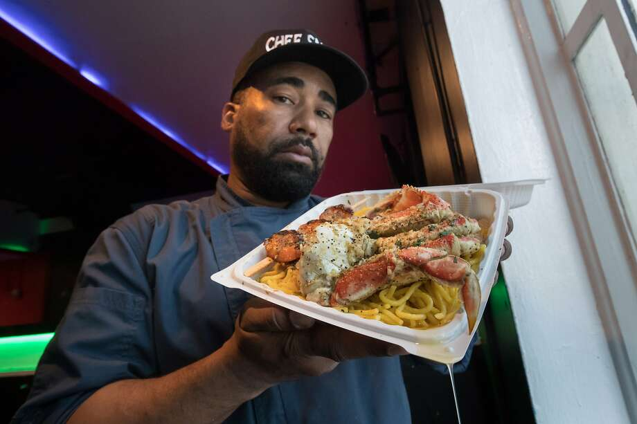 Edward Wooley (Chef Smelly) holds his popular half crab on garlic noodles dish. Photo: Paul Kuroda, Special To The Chronicle