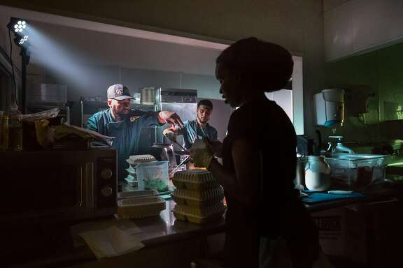 Edward Wooley (Chef Smelly), Juan Martinez and Indigo Burris-Albans works under emergency lighting when the lights failed in the kitchen on Friday, May 19, 2017 in Oakland, Calif.