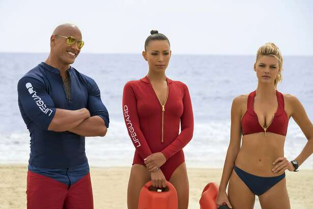 "This image released by Paramount Pictures shows Dwayne Johnson as Mitch Buchannon, from left, Ilfenesh Hadera as Stephanie Holden and Kelly Rohrbach as CJ Parker in ""Baywatch."" (Frank Masi/Paramount Pictures via AP)"