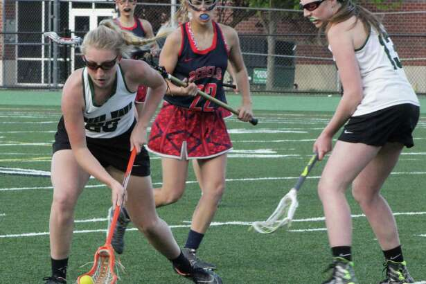 The New Milford High School girls varsity lacrosse team recently faced off against New Fairfield. The Green Wave beat New Fairfield 14-4. Above, senior Chloe Knight scoops up the ball.