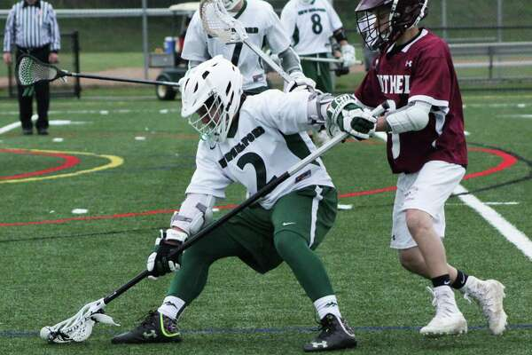 The New Milford High School varsity lacrosse faced off against Bethel May 9. Green Wave won the game 16-2. Above, sophomore Devin Cera holds off his Bethel opponent to scoop the ball.