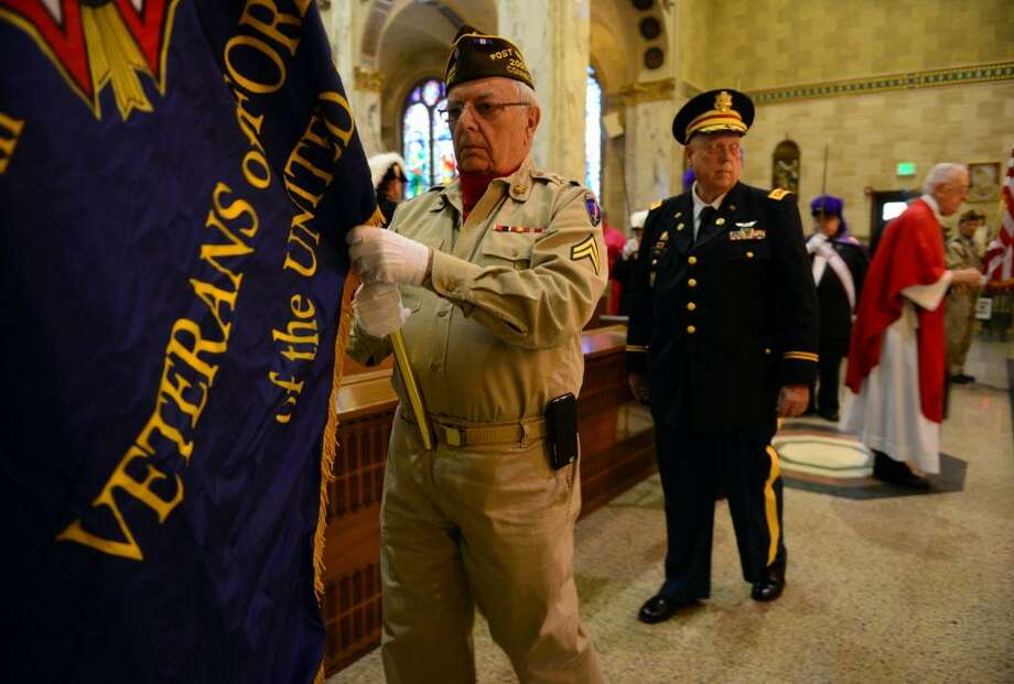James Santangelo, a member of VFW Post 9617, is part of the color guard at the start of a veterans mass at Holy Name of Jesus Roman Catholic Church in Stamford, Conn., on Saturday May 23, 2015. Behind Santangelo is Cortland E. Mehl, Commander of the CWV chapter. The mass was sponsored by the Stamford chapters of the Knights of Columbus, Kulka Brothers Post 1957 of the Catholic War Veterans and VFW Post 9617. Overseeing the mass was Msgr. Thaddeus F. Malanowski. Photo: Christian Abraham / Christian Abraham / Connecticut Post
