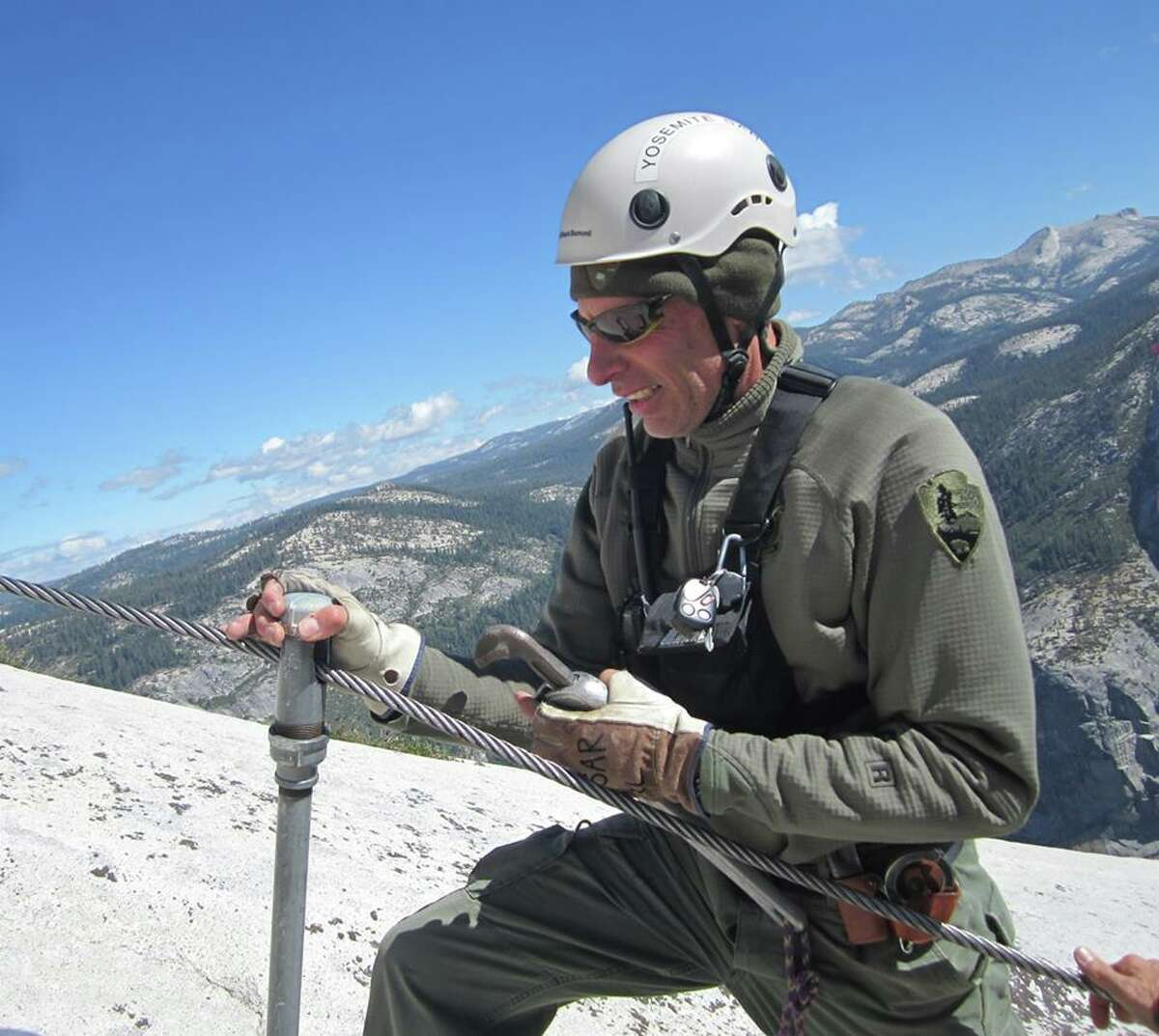 A Yosemite National Park official installing cables on Half Dome.