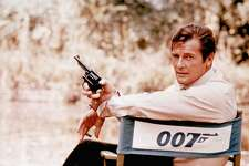 FILE - British actor Roger Moore, playing the title role of secret service agent 007, James Bond, is shown on location in England in 1972. Moore, played Bond in seven films, more than any other actor.  Roger Moore's family said Tuesday May 23, 2017 that the  former James Bond star has died after a short battle with cancer  (AP Photo, File)