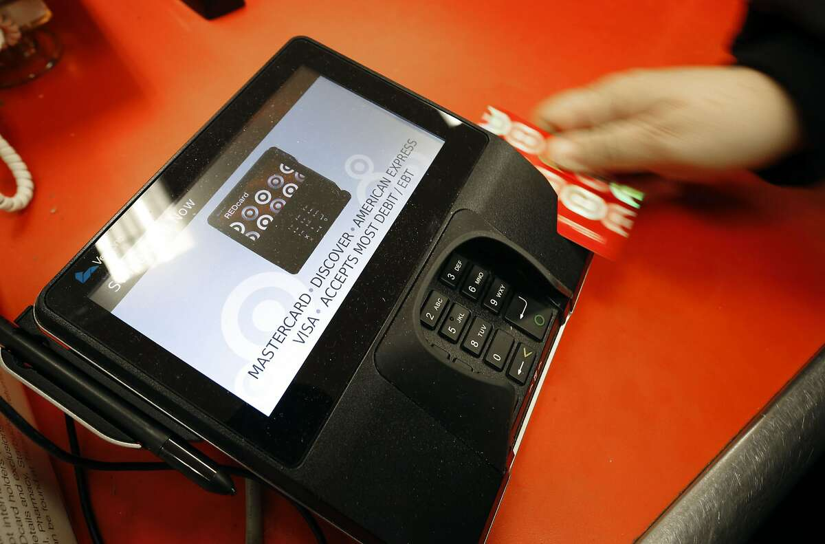 FILE - In this Nov. 28, 2014, file photo, a shopper pays for her purchases at a Target store in South Portland, Maine. The Federal Reserve releases consumer credit data for September on Friday, Nov. 6, 2015. (AP Photo/Robert F. Bukaty. File)