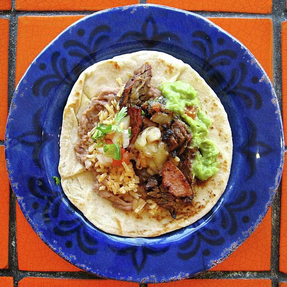 Fajita taco with beef fajitas, bacon, sausage, cheese, rice, beans, guacamole and pico de gallo on a handmade flour tortilla from Fajita Taco Place. Photo: Mike Sutter /San Antonio Express-News