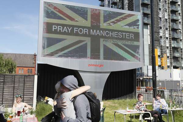 A couple embrace under a billboard in Manchester city centre, Tuesday May 23, 2017, the day after the suicide attack at an Ariana Grande concert that left 22 people dead as it ended on Monday night. (AP Photo/Kirsty Wigglesworth)