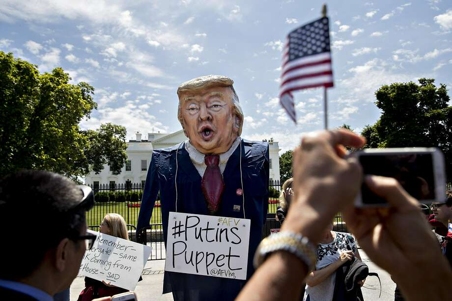 A demonstrator wears an effigy with President Trump's likeness with a sign referencing his ties to Russia at a protest outside the White House this month. Photo: Andrew Harrer, Bloomberg