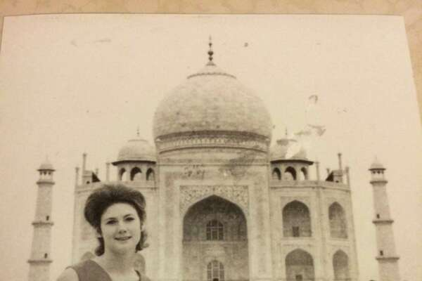 Sandee Mewhinney poses in front of the Taj Mahal in Acra, India, during an around-the-world trip she took in 1969.