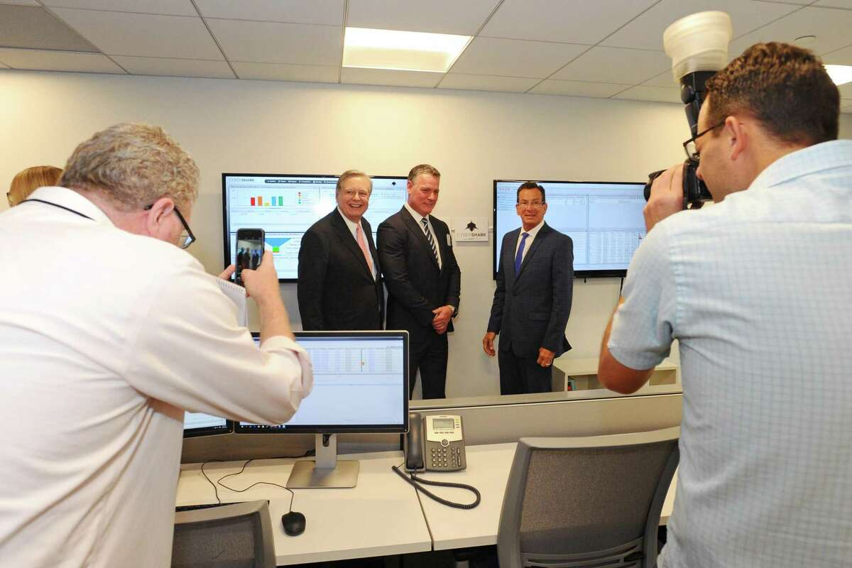From center left, Stamford Mayor David Martin, BlackStratus CEO Dale Cline and Gov. Dannel P. Malloy pose for a photo after the grand opening of cyber-security firm BlackStratus' offices at 9 W. Broad St., on June 28, 2016.
