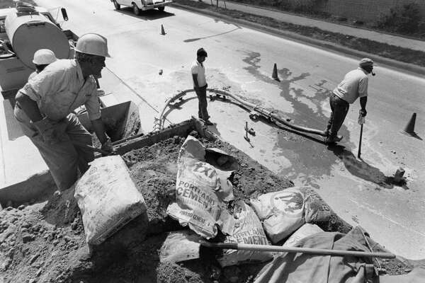 May 18, 1977: Workers with the City of Houston street repair department drill holes and pump mud and cement under the roadway at 4800 Woodway in an attempt to level the street to prevent runoff water from collecting in a dip in the street.