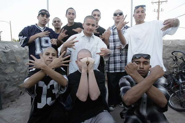 "In this photo released 19 April, 2006, members of the Pico Norte 19th Street gang pose flashing their hand signs in El Paso, Texas. The gang, an offshoot of ""Los Juaritos"" gang from Ciudad Juarez, Mexico, grew into one of the most notorious gang in the city with some 60 active members. The gang was known also for being a ""clean gang"" not involved in drug trafficking or part of older gangs that have become involved in large organize crime schemes. Some 650 known gang, the majority of hispanic-origin, operate in El Paso, according to the Onramp Youth Foundation, an organization that provides council to youths in trouble. Members say they joined the gang  to gain respect among their peers and to protect themselves against other gangs, they consider the group a part of their family."