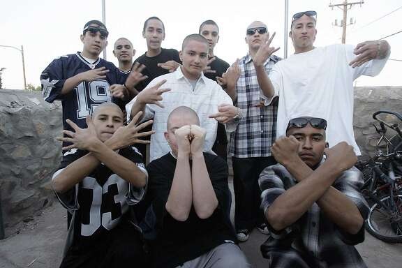 """In this photo released 19 April, 2006, members of the Pico Norte 19th Street gang pose flashing their hand signs in El Paso, Texas. The gang, an offshoot of """"Los Juaritos"""" gang from Ciudad Juarez, Mexico, grew into one of the most notorious gang in the city with some 60 active members. The gang was known also for being a """"clean gang"""" not involved in drug trafficking or part of older gangs that have become involved in large organize crime schemes. Some 650 known gang, the majority of hispanic-origin, operate in El Paso, according to the Onramp Youth Foundation, an organization that provides council to youths in trouble. Members say they joined the gang  to gain respect among their peers and to protect themselves against other gangs, they consider the group a part of their family."""