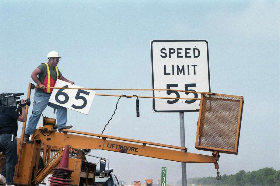 Crews on the westbound lanes of the Katy Freeway just west of Katy put up the first 65 mph road sign in the area, May 8, 1987. Photo: E. Joseph Deering, Houston Chronicle