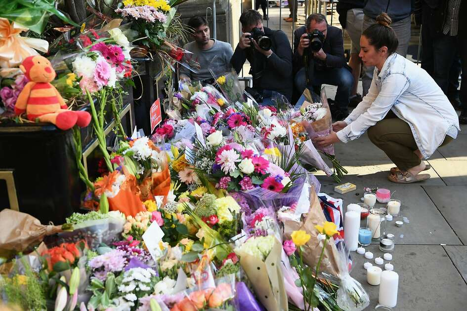 MANCHESTER, ENGLAND - MAY 23:  A member of the public lays flowers at a candlelit vigil, to honour the victims of Monday evening's terror attack, at Albert Square on May 23, 2017 in Manchester, England. Monday's explosion occurred at Manchester Arena as concert goers were leaving the venue after Ariana Grande had just finished performing. Greater Manchester Police are treating the explosion as a terrorist attack and have confirmed 22 fatalities and 59 injured.  (Photo by Jeff J Mitchell/Getty Images)