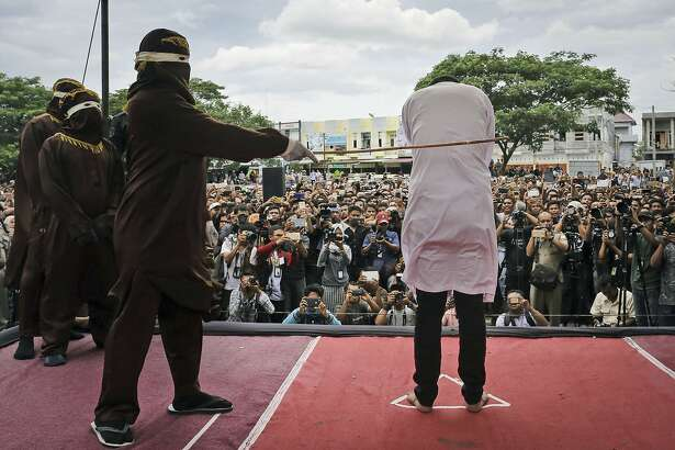 "Shariah law official whips one of two men convicted of gay sex during a public caning outside a mosque in Banda Aceh, Aceh province Indonesia, Tuesday, May 23, 2017. Two men in the province were publicly caned dozens of times Tuesday for consensual sex, a punishment that intensifies an anti-gay backlash and which rights advocates denounced as ""medieval torture."" (AP Photo/Heri Juanda)"