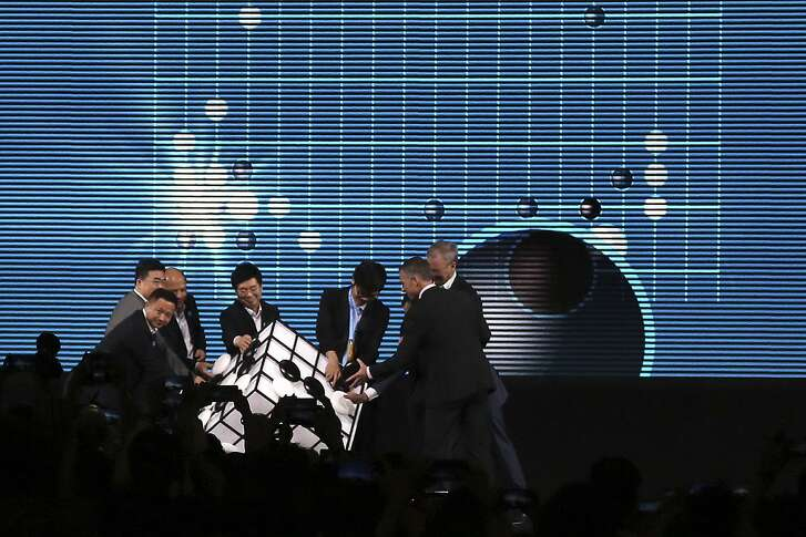 Go player Ke Jie of China, third from right, and other participants place pieces on a checkered cube during the opening ceremony of the Future of Go Summit in Wuzhen in eastern China's Zhejiang Province, Tuesday, May 23, 2017. Ke Jie, the world's top-ranked Go player, started a three-round showdown on Tuesday against Google's artificial intelligence program, AlphaGo, which beat a South Korean Go master in a five-round showdown last year. (AP Photo/Peng Peng)