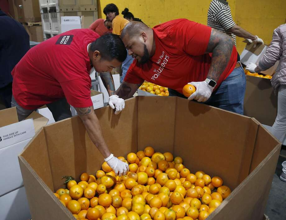 Volunteers Jeff Santiago (left) and Kenny King fill boxes of oranges from a larger container at the SF-Marin Food Bank. Photo: Paul Chinn, The Chronicle