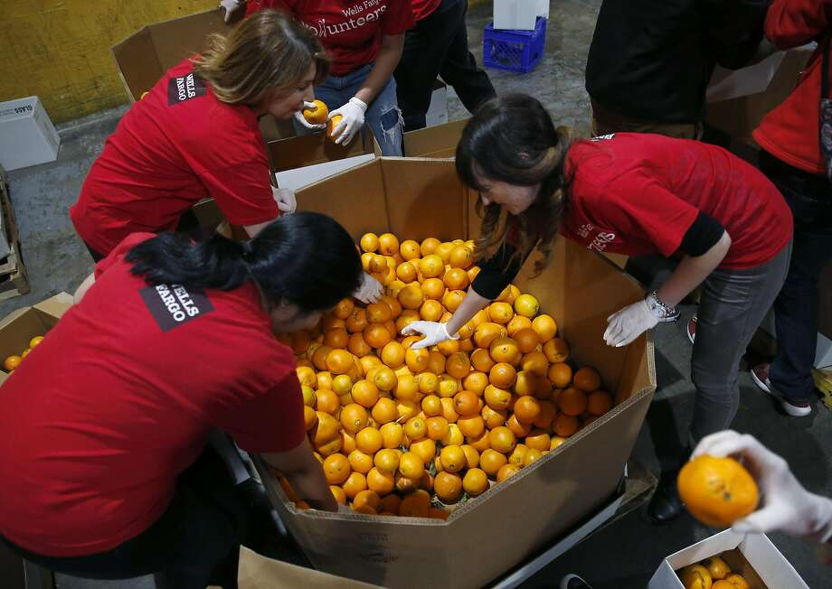 A group of volunteers sort and pack boxes of oranges at the SF-Marin Food Bank in San Francisco, Calif. on Tuesday, May 23, 2017. Photo: Paul Chinn, The Chronicle