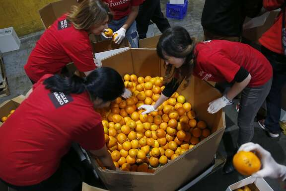 A group of volunteers sort and pack boxes of oranges at the SF-Marin Food Bank in San Francisco, Calif. on Tuesday, May 23, 2017.