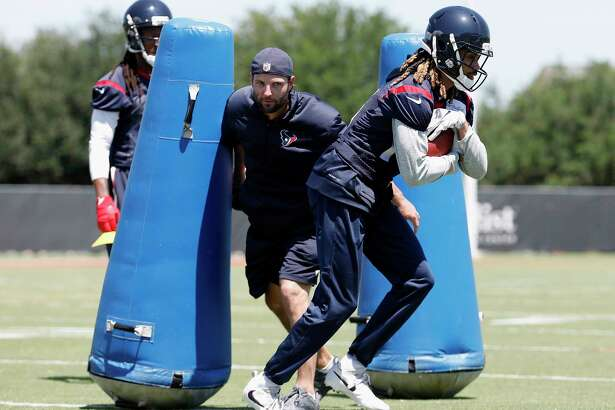 Offensive and special teams assistant coach Wes Welker attempts to strip the ball from Houston Texans wide receiver  Will Fuller (15) during the Houston Texans OTAs at the Methodist Training Center in Houston, TX on Tuesday, May 23, 2017.