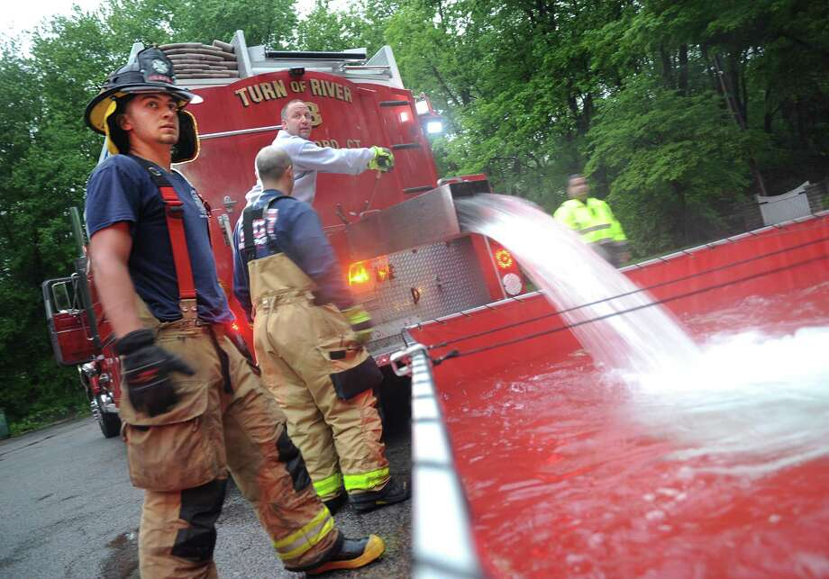Long Ridge firefighter John Spoto, left, watches over as a tanker unloads water during a firefighters' drill in northern Stamford, h to discard the water into large pools. Belltown firefighter Jason Kane controls the switches as water is pumped from a pond into a tanker Photo: Tyler Sizemore / Hearst Connecticut Media / Greenwich Time