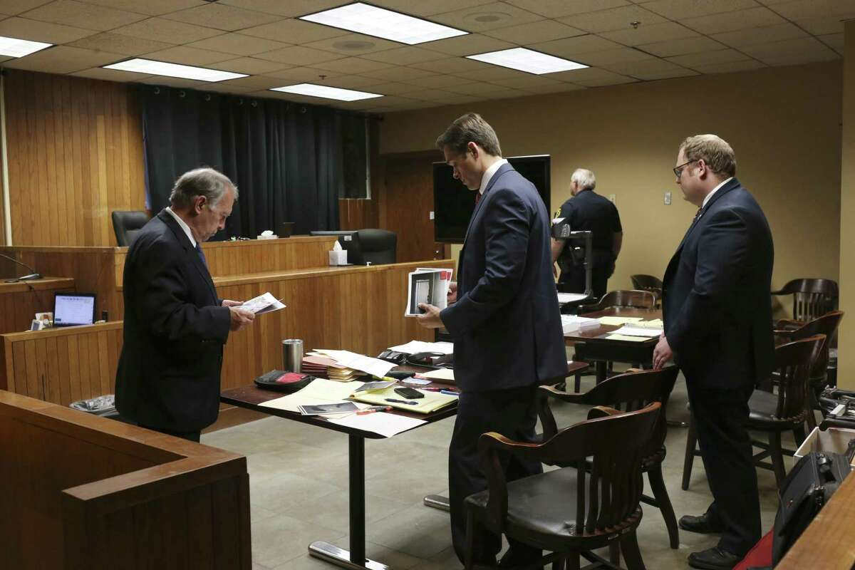 Defense attorney Ron Ross, left, goes over exhibits with Prosecutors Joshua Somers, center, and James Phillips during a murder trail in Bexar County Impact Court, Monday, May 8, 2017. Judge Laura Parker presides over the court, located in the basement of the Bexar County Courthouse, and is designed to take some of the cases from courts that have huge dockets while also reducing the overpopulation problem at the Bexar County Jail.
