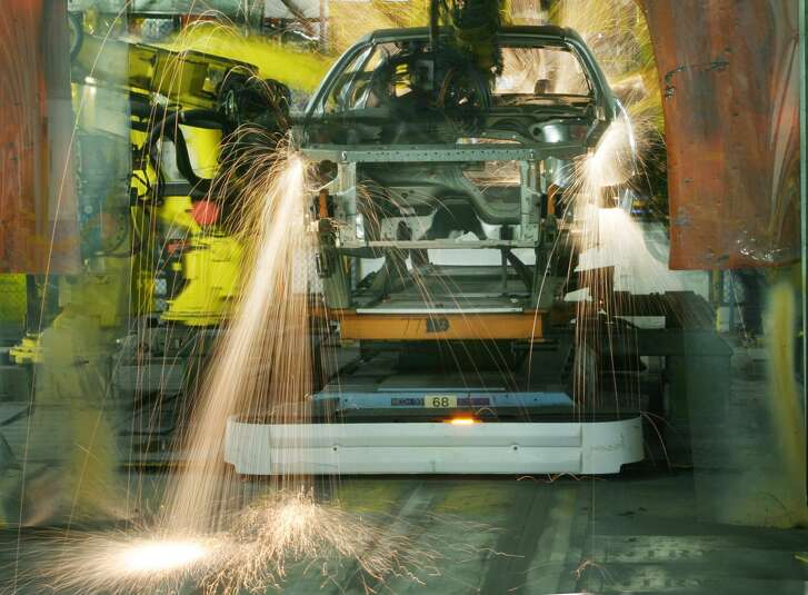 Robotic welders work on a vehicle at General Motors (Canada) Corp.'s plant in Oshawa, Ontario in 2005. Such innovations spur fears of job losses. This happens, but with more productivity, other jobs are created.