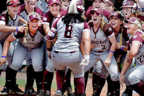 The Texas A&M softball team cheers teammate Tori Vidales (8) as she touches home plate after a solo home run in the Aggies 3-1 victory over the Texas Longhorns during the NCAA college softball championship tournament in College Station, Texas, Sunday, May 21, 2017. (Dave McDermand/College Station Eagle via AP)