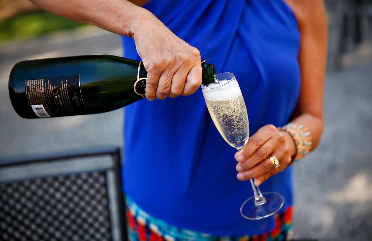Annie Tomasello, of Gilroy, pours glasses of bubbly on the patio at Domaine Chandon in Yountville, Calif., on Tuesday, October 13, 2015.