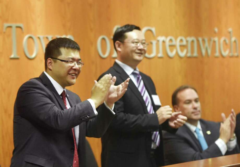 Tao Guo, left, Head of Hangzhou Hedge Funds Association, Dr. Chengtao Jin, center, District Chief of Shangchecg District, Hangzhou, and Greenwich First Selectman Peter Tesei applaud the Greenwich-Hangzhou Sister City Agreement Singing Ceremony at Town Hall in Greenwich, Conn. Tuesday, May 23, 2017. Delegates from Hangzhou, China visted Greenwich Tuesday to sign an agreement making Greenwich and Hangzhou sister cities. Hangzhou is also a major hedge fund city, located outside of Shanghai. Photo: Tyler Sizemore / Hearst Connecticut Media / Greenwich Time