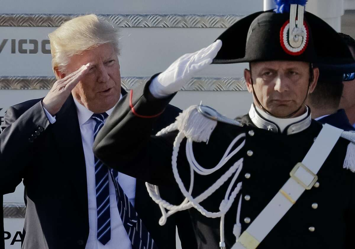 US President Donald Trump salutes a Carabinieri paramilitary officer upon his arrival at Fiumicino's Leonardo Da Vinci International airport, near Rome, Tuesday, May 23, 2017. Trump is in Italy for a two day visit, including a meeting with Pope Francis at the Vatican, ahead of his participation in a NATO meeting in Brussels on Thursday. (AP Photo/Andrew Medichini)
