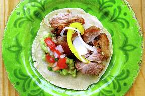 Carnitas taco with guacamole, pico de gallo and escabeche on a handmade corn tortilla from Carnitas Lonja.