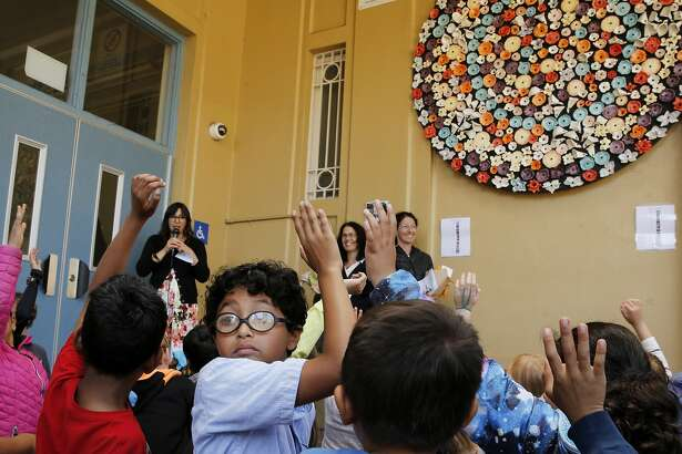 Brandon Fierro Mart�nez raises his hand to show he worked on the wreath at Buena Vista Horace Mann on Tuesday, May 23, 2017, in San Francisco, Calif. Students made the ceramic wreath that symbolizes a celebration of diversity.