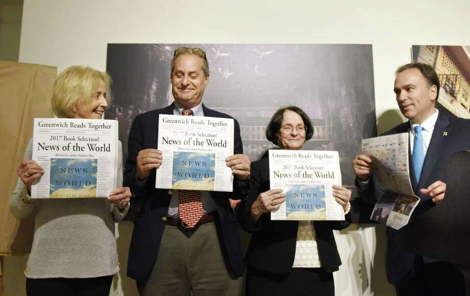 """From left, Friends of Greenwich Library Chair Sharon Fortenbaugh, Greenwich Library Board of Trustees President Chip Haslun, Greenwich Library Director Barbara Ormerod-Glynn, and Greenwich First Selectman Peter Tesei unveil the 2017 Greenwich Reads Together book """"News of the World"""" at Greenwich Library in Greenwich, Conn. Tuesday, May 23, 2017. The 2016 novel """"News of the World,"""" by Paulette Jiles, was chosen as the book for the community-wide reading experience. The middle school companion book chosen was """"The Ransom of Mercy Carter,"""" by Caroline B. Cooney, and the elementary school companion chosen was """"The Girl Who Loved Wild Horses,"""" by Paul Goble. Photo: Tyler Sizemore / Hearst Connecticut Media / Greenwich Time"""