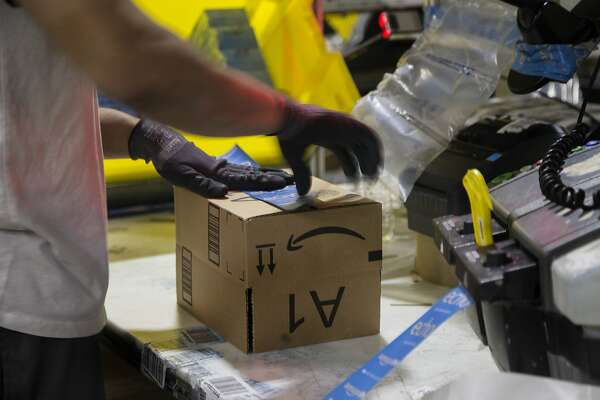 A worker tapes a box while packing items on Cyber Monday at the Amazon Fulfillment Center on Nov. 28, 2016 in San Bernardino, Calif. (Gina Ferazzi/Los Angeles Times/TNS)