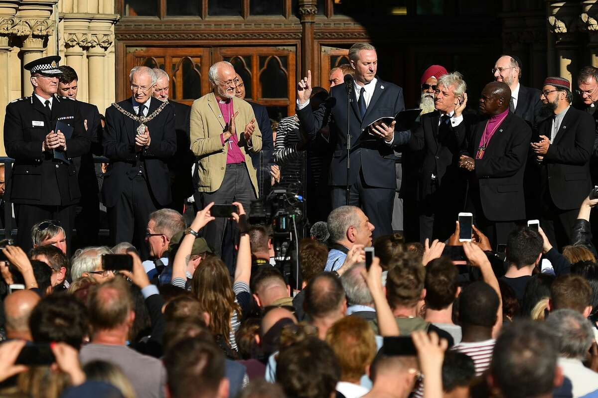 Poet Tony Walsh (C) gestures as he reads a poem during a vigil in Albert Square in Manchester, northwest England on May 23, 2017, in solidarity with those killed an injured in the May 22 terror attack at the Ariana Grande concert at the Manchester Arena. Twenty two people have been killed and dozens injured in Britain's deadliest terror attack in over a decade after a suspected suicide bomber targeted fans leaving a concert of US singer Ariana Grande in Manchester. British police on Tuesday named the suspected attacker behind the Manchester concert bombing as Salman Abedi, but declined to give any further details. / AFP PHOTO / Ben STANSALL (Photo credit should read BEN STANSALL/AFP/Getty Images)