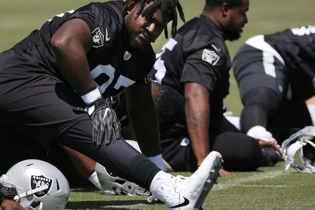 Mario Edwards Jr. stretches with teammates during practice at the Raiders' Alameda facility.