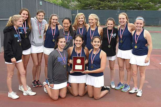 The Darien girls tennis team celebrates its second straight FCIAC championship by posing with the trophy after defeating Staples in the title match 4-3 on Tuesday at Wilton High School.