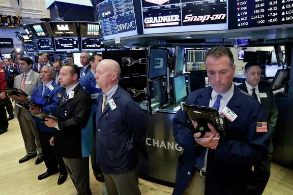 Traders on the floor of the New York Stock Exchange, Tuesday, May 23, 2017, observe a moment of silence in the wake of the attack in Manchester, England. (AP Photo/Richard Drew)